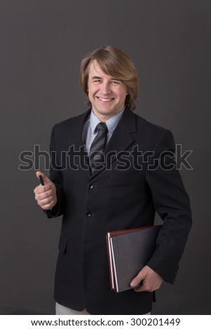 Businessman happy smiling isolated on dark grey. Middle-haired man in black business suit posing with documents and a pen.