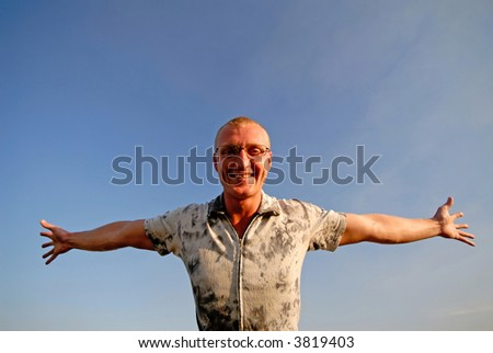 businessman has joyfully dissolved hands on  background of  dark blue sky