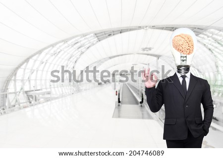 businessman have brain inside a light bulb posed gesturing ok sign while standing at futuristic airport interior with concept of real estate and engineering for success business creativity - stock photo