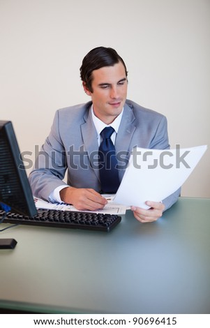 Businessman having a look at a contract in his hand - stock photo