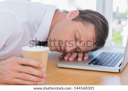 Businessman having a nap on his laptop while he is holding a cup of coffee - stock photo