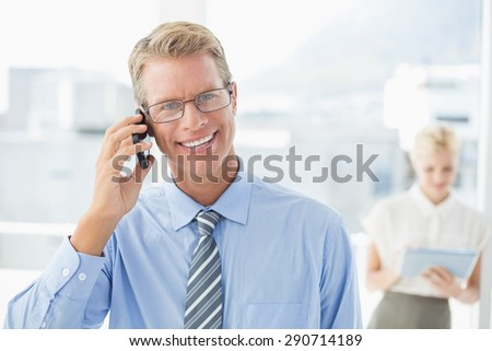 Businessman having a phone call with colleague in background in an office - stock photo