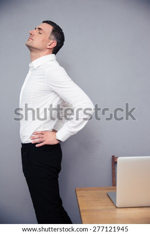 Businessman having backache in office - stock photo