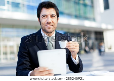 Businessman having breakfast and reading his tablet - stock photo