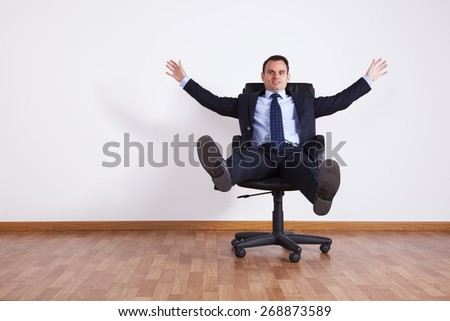 Businessman having fun with his chair - stock photo