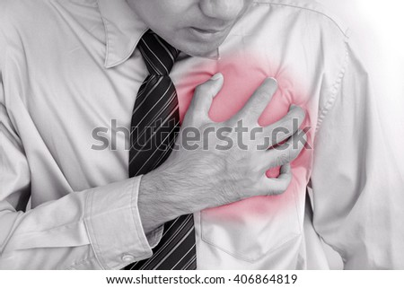 Businessman having heart attack - monochrome effect with red spot on pain area - stock photo