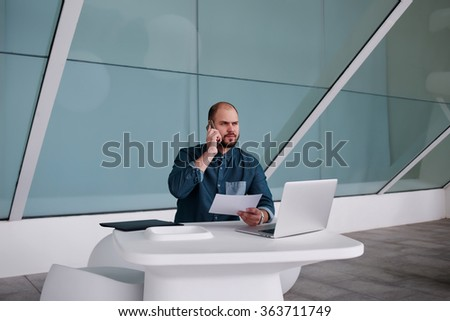 Businessman having serious conversation on cell telephone while sitting in front of open net-book with paper documents in hand, male entrepreneur talking on mobile phone during work on laptop computer - stock photo