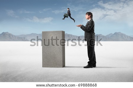 Businessman helping a smaller one to jump on a high cube - stock photo