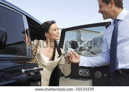Businessman helping Woman Get Out of Car parked near private jet, side view - stock photo