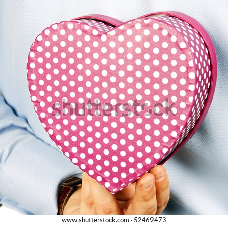 Businessman hiding a heart gift - stock photo