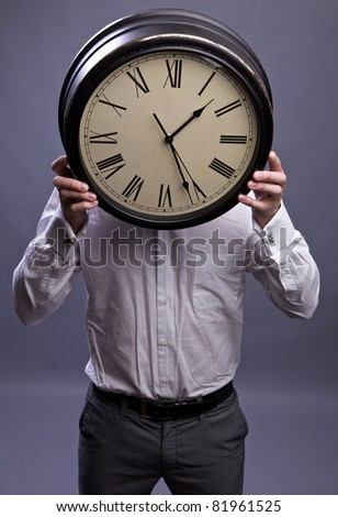Businessman hiding behind the big clock. Time for work concept - stock photo