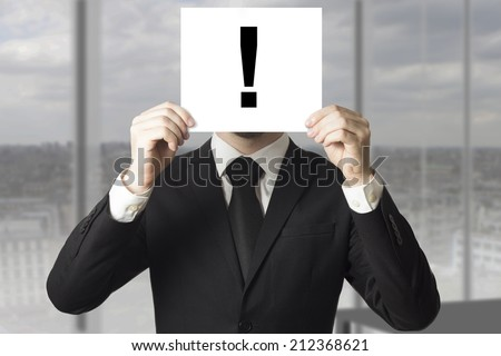 businessman hiding face behind exclamation mark sign - stock photo
