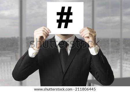 businessman hiding face behind hash tag symbol - stock photo