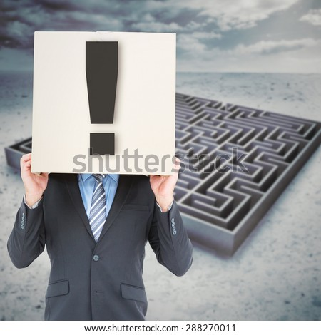 Businessman hiding head with a box against big maze under cloudy sky - stock photo