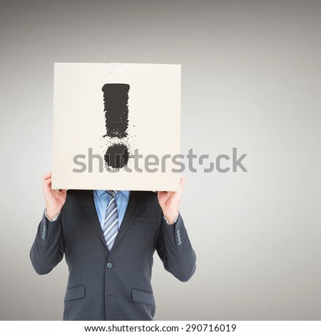 Businessman hiding head with a box against grey vignette - stock photo