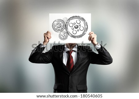 Businessman hiding his face behind paper with drawing - stock photo