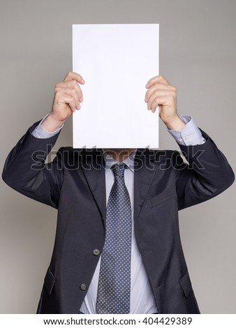 businessman hiding his face with a white copyspace billboard on gray background - stock photo