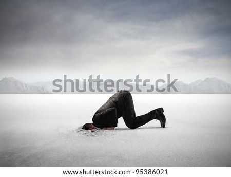 Businessman hiding his head in the sand - stock photo