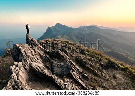 businessman hike on the peak of rocks mountain at sunset, success,winner, leader concept - stock photo