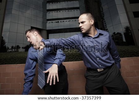 Businessman hitting another businessman
