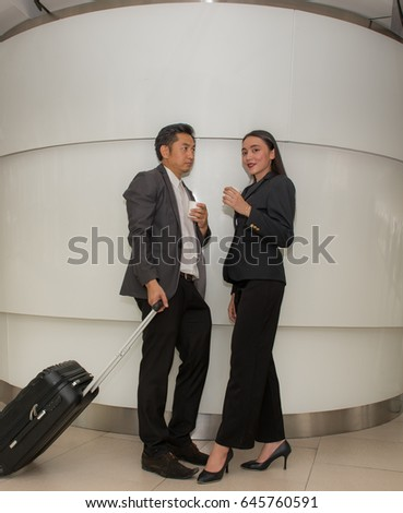 Businessman hold a luggage case in the city ,  Businessman and businesswoman talking about business and drinking coffee ,
