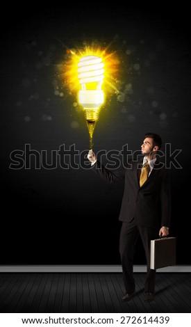 Businessman hold a shining eco-friendly idea bulb on a black background - stock photo