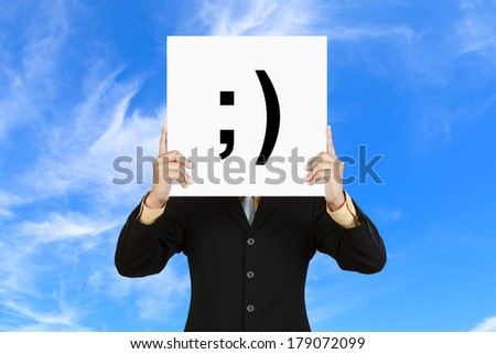 Businessman hold board with smile face emoticon on blue sky background - stock photo