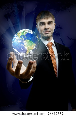 businessman hold in hand terrestrial globe, on dark blue background image planet by: Stokli, Nelson, Hasler Laboratory for Atmospheres Goddard Space Flight Center www.rsd.gsfc.nasa.gov/rsd - stock photo