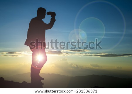 Businessman hold laptop and watch binoculars for his vision on the high mountain  - stock photo
