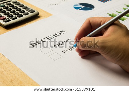 Businessman hold pen for approve and reject decision with calculator and financial graph support