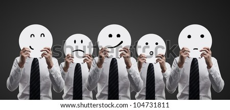 businessman hold plates with smilies on black background - stock photo