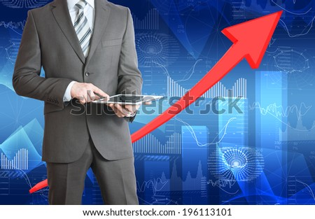 Businessman hold tablet. Red arrow and glowing graphs as backdrop