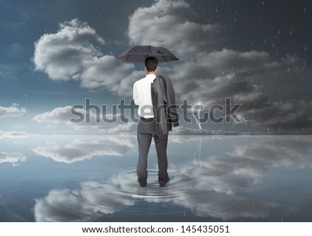 Businessman holding a black umbrella during stormy weather