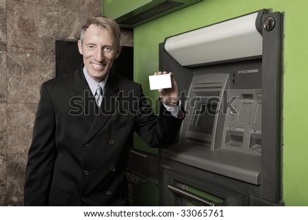 Businessman holding a blank business card by an atm machine