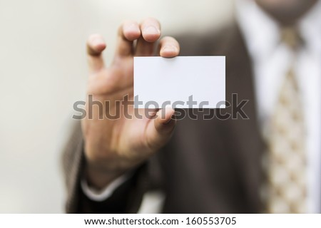 businessman holding a blank card in the hand - stock photo