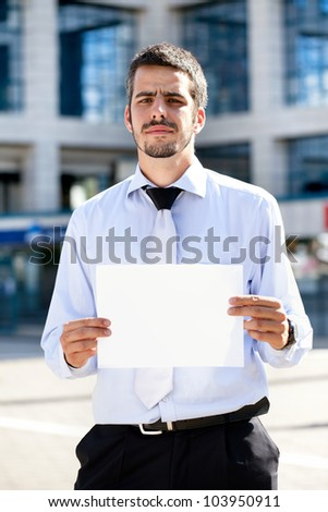Businessman holding a blank sign front of office building