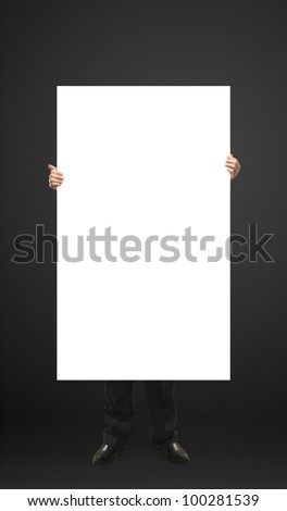 Businessman holding a blank white board. Male hands holding a blank white panel. On a black background - stock photo