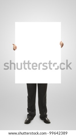 Businessman holding a blank white board. Male hands holding a blank white panel. On a gray background - stock photo