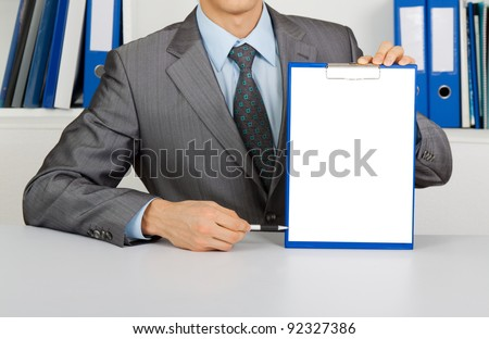 businessman holding a blank white board, signboard, clipboard with paper, point finger with pen on an empty bill board with copy space for text, unrecognizable person sitting at the desk at office - stock photo