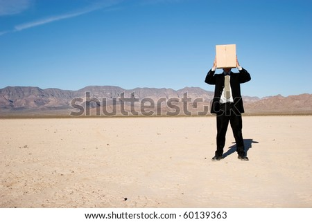 Businessman holding a box over his head - stock photo