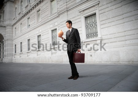 Businessman holding a briefcase and a money box on a city street - stock photo