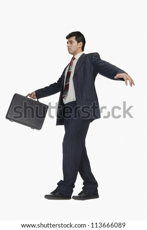 Businessman holding a briefcase and walking carefully - stock photo