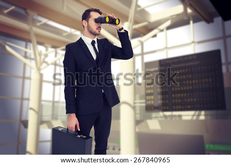 Businessman holding a briefcase while using binoculars against airport - stock photo