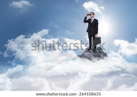 Businessman holding a briefcase while using binoculars against mountain peak through the clouds - stock photo