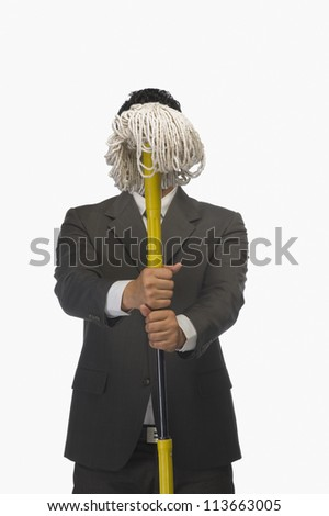 Businessman holding a broom in front of his face - stock photo