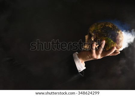 Businessman holding a burning globe while they changed into a skull - stock photo