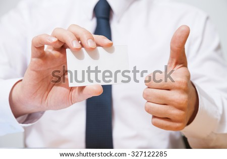 Businessman holding  a business card and showing a thumb up sign - closeup shot - stock photo