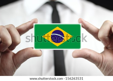 Businessman holding a business card with a Brazil Flag - stock photo