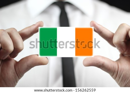 Businessman holding a business card with a Ireland Flag - stock photo