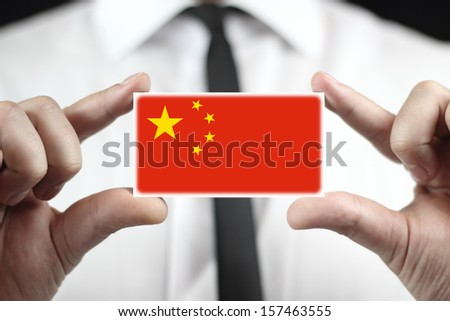 Businessman holding a business card with China Flag - stock photo
